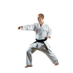 On an isolated white background, an athlete trains formal karate exercises