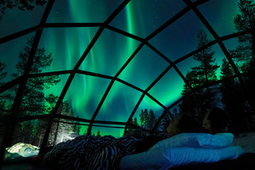 CLOSE UP Young Caucasian tourist couple observing the night sky from a cool glass house in the Scandinavian wilderness. Girlfriend and boyfriend enjoying a romantic evening in a cool glassy igloo.