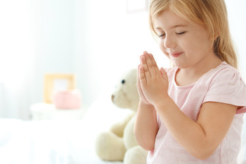 Little girl praying in bed at home. Space for text