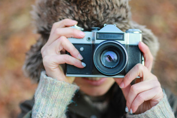 Young woman taking pictures  the autumn park. Concept  photographer