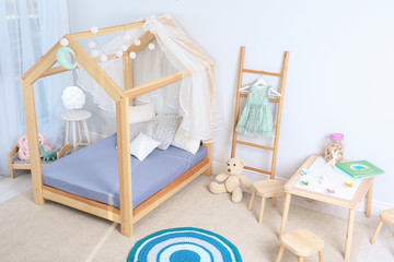 View of cozy child's room interior with cute bed