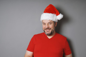 smiling middle aged man with graying beard wearing santa hat and red t-shirt - real people christmas concept