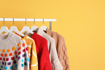 Collection of warm sweaters hanging on rack against color background. Space for text