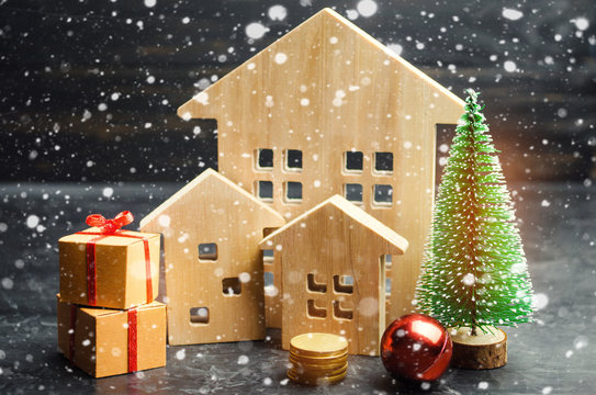 Wooden houses and Christmas tree. Christmas Sale of Real Estate. New Year discounts for buying house. Purchase apartments at a low price. Winter resort and vacation. Holiday discounts