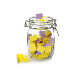Colorful paper pieces for lottery in glass jar on white background