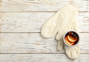 Fototapete - Cup of hot winter drink and warm knitted mittens on wooden background, top view with space for text. Cozy season