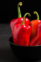 Red peppers in plate on black background - closeup photo of whole fresh ripe sweet vegetables in dark mood style.