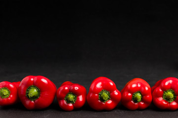 Red peppers in line on black background - closeup photo of whole fresh ripe sweet vegetables in dark mood style.