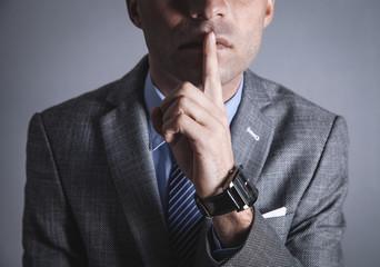 Caucasian man making silence gesture.