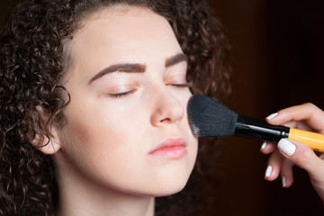 Closeup portrait of beautiful woman getting professional make-up with brush. Beauty and makeup concept
