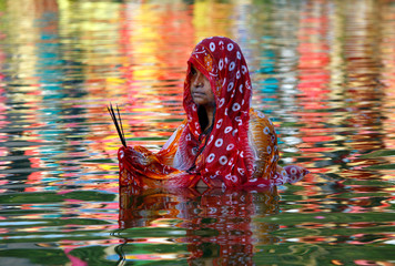 A Hindu woman worships the Sun god in the waters of a lake during the religious festival of Chhath Puja in Agartala