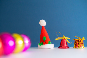 Poster Regenboog Christmas Concept with copy space.Small Santa Claus hat with ornament balls,bell,pineconse and small present.