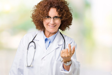Middle ager senior doctor woman over isolated background Beckoning come here gesture with hand inviting happy and smiling