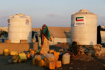 Women collect water from a charity tap at a camp sheltering displaced people from the Red Sea port city of Hodeidah near Aden, Yemen