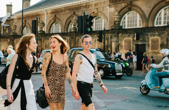 three friends walking and talking together in London