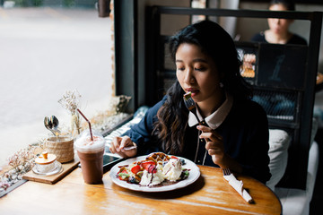 Asian woman eating dessert in the cafe