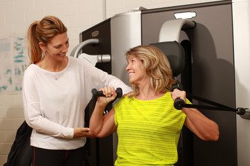 Personal trainer gives instructions to a mature woman