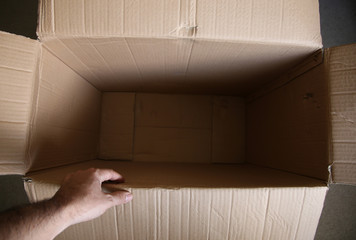 A man touching an empty box. Packaging and shipping concept image.