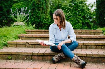 female gardener sitting on steps checking plans