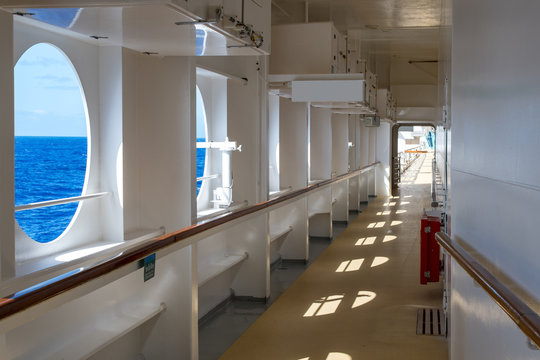 Promenade deck of a cruise ship on a Sunny day with views of the sea horizon.