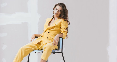 Young female /fashion model in abstract white space with yellow outfit.
