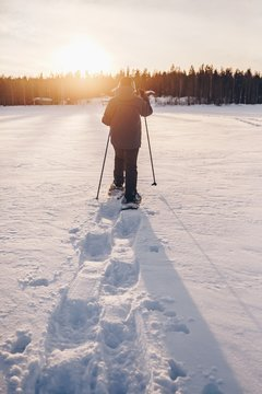 Man in snowshoes is walking with beautiful sunrise light.