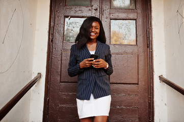 Success stylish african american woman in jacket and skirt against old wooden door with smartphone at hands.
