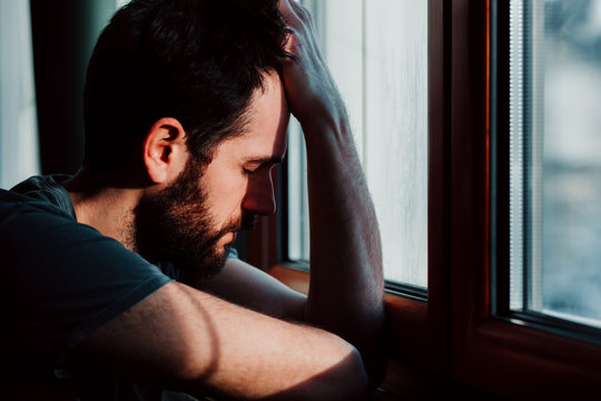 Bearded young man by the window in despair