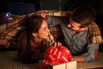 Young woman opens a gift which she got from her husband.Christmas evening  concept.