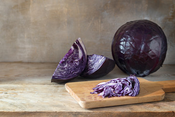 red cabbage whole and slices on a cutting board on a rustic wooden table, copy space