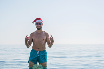 Christmas holidays in tropical countries, a man in a Santa Claus hat on the beach, free space.