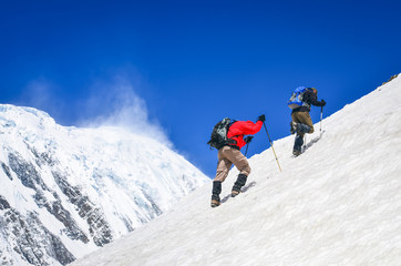 Two mountain trekkers on steep snowed hill with peaks background