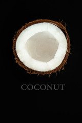 one half of ripe coconut on black background,top view