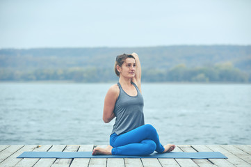 Beautiful young woman practices yoga asana Gomukhasana - Cow face pose on the wooden deck near the lake