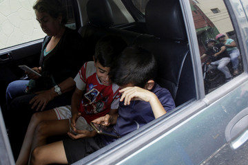 Children play with a cell phone while they wait in a car for gas near a gas station of the Venezuelan state-owned oil company PDVSA in San Cristobal