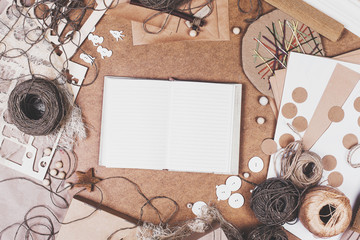 Hobby. Notebook for records, skeins of rope, buttons, paper and other office supplies on Kraft background. In the studio