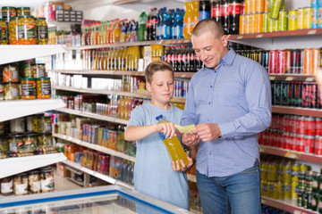 Man with boy choosing goods together with shopping list in store