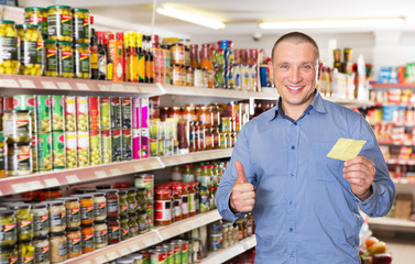 Man holding shopping list while choosing products