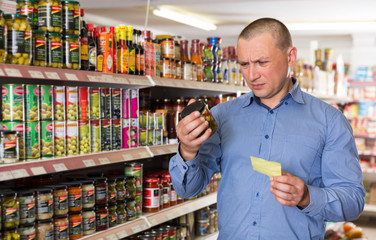 man purchasing food products on shopping list