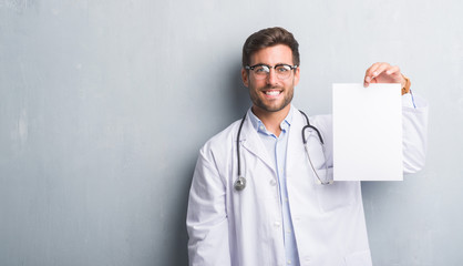 Handsome young doctor man over grey grunge wall holding blank sheet contract with a happy face standing and smiling with a confident smile showing teeth
