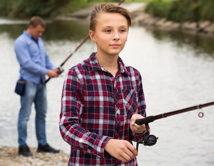 Boy casting line for fishing on lake