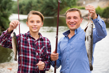 Young father with son looking at fish on hook