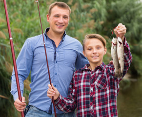 Glad father with son looking at fish on hook