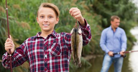 Positive teenage boy releasing catch on hook fish