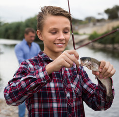 teenager boy holding catch fish on hook  .