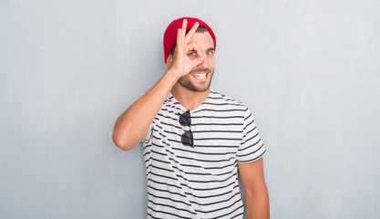 Handsome young hipster man over grey grunge wall wearing navy t-shirt and wool cap doing ok gesture with hand smiling, eye looking through fingers with happy face.