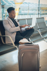 Young businessman is seated in the airport working with a laptop and carrying a suitcase waiting for his flight
