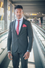 Young businessman stands up outside of the airport looking at the camera