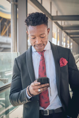 Young businessman going to the airport looking his telephone and smiling