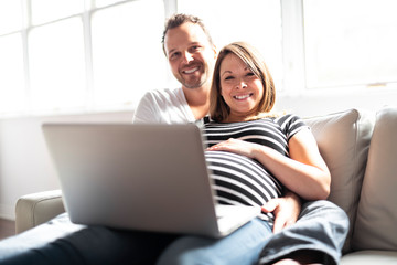 A Couple With Pregnant Woman Using Laptop Computer Together Wall mural